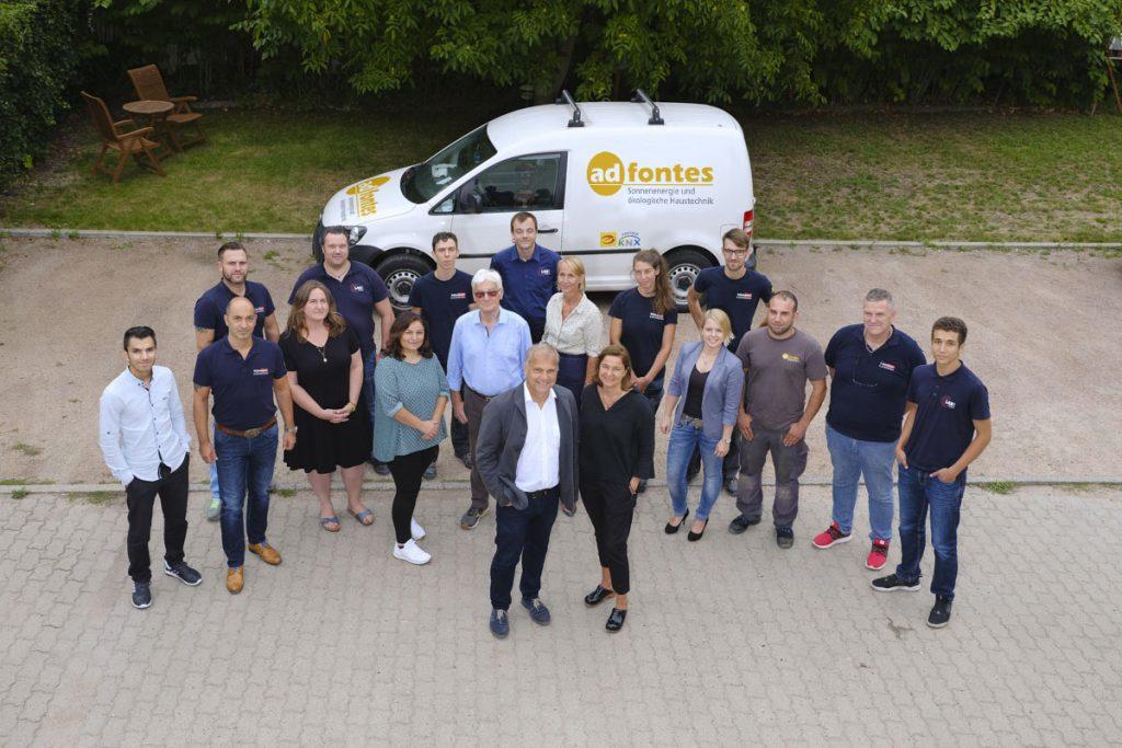 Das ad fontes Team auf den Firmengelände vor ein Firmenwagen