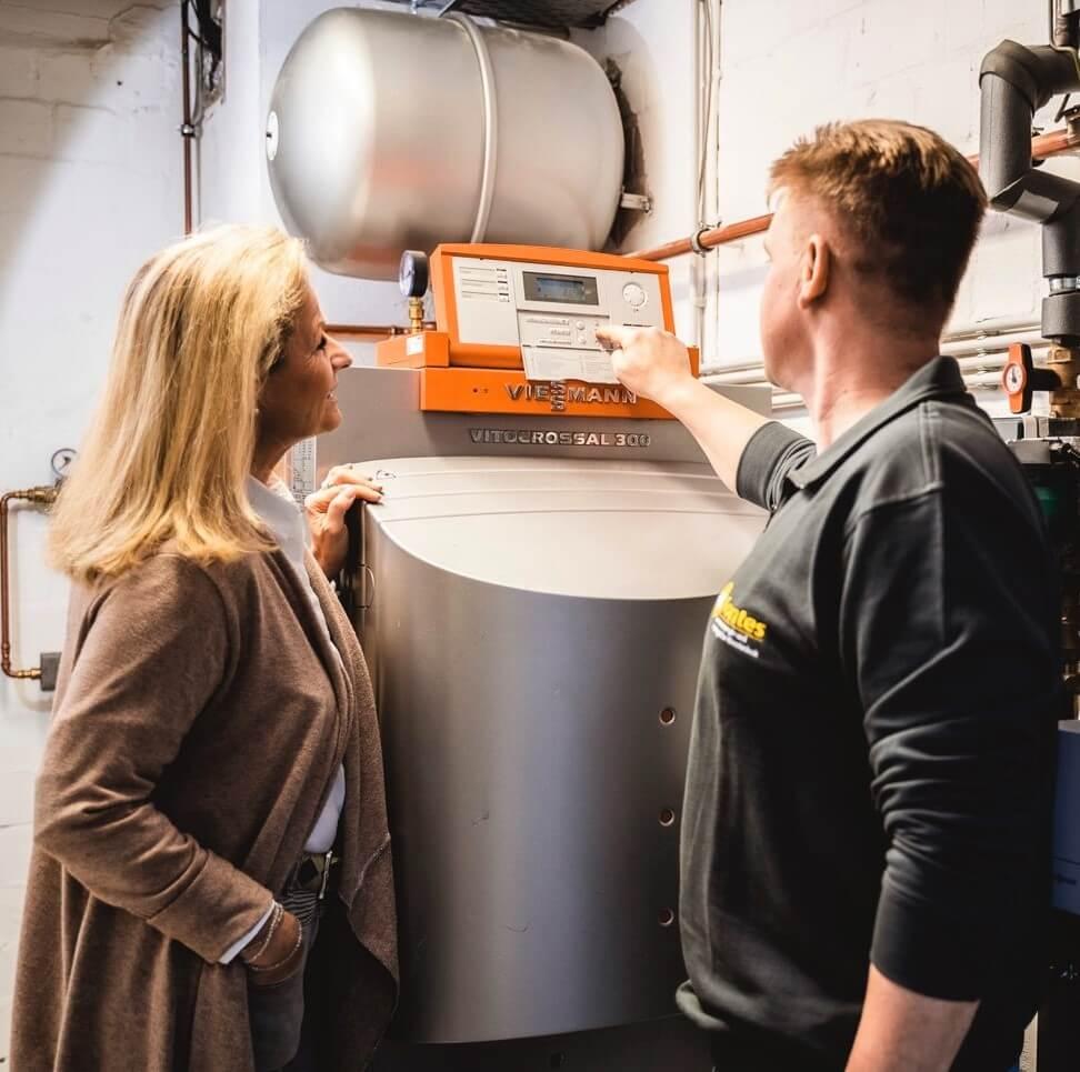 Ein Monteur stellt den Gasbrennwertkessel bei Installation der Gasheizung ein.